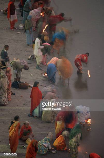"""Hindu pilgrims preparing to offer small oil lamps in a prayer of offering known as """"Puja"""" to the holy Ganges River. The pilgrims have flocked to the..."""