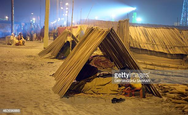 Hindu pilgrims rest near temporary tents before taking a holy dip during an auspicious time at the Gangasagar island around 160 kms south of Kolkata...