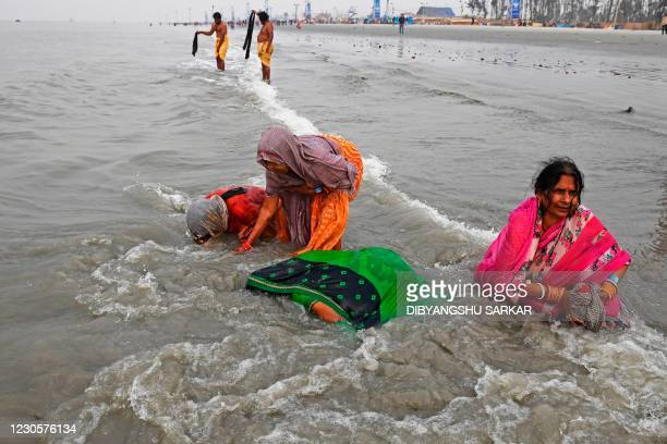 Hindu pilgrims take a holy dip at the confluence of Ganges and the Bay of Bengal during the Gangasagar Mela on the occasion of Makar Sankranti, a day...