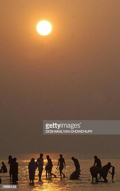 Hindu pilgrims take a holy dip during the sunset in Sagar Island 14 January 2004 some 150 kms south of Calcutta Thousands of pilgrims gather on the...