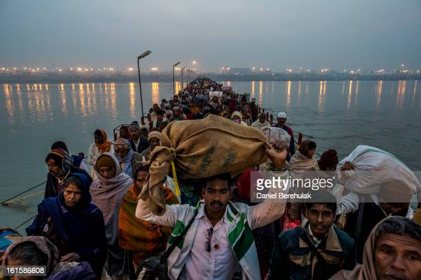 Hindu pilgrims walk across a pontoon bridge as others bathe on the banks of Sangam the confluence of the holy rivers Ganges Yamuna and the mythical...