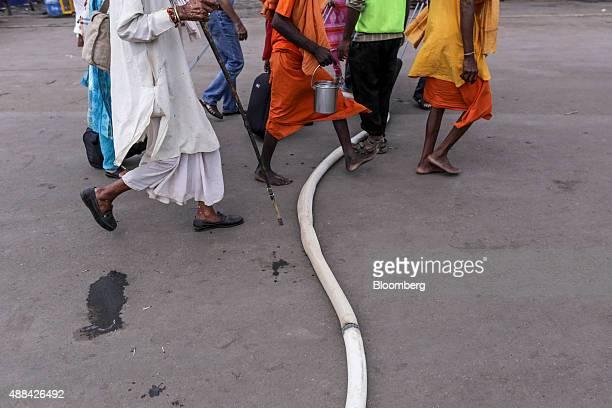 Hindu pilgrims walk over a temporary water pipe running over a road in Nashik, Maharashtra, India, on Saturday, Sept. 12, 2015. Millions of pilgrims...