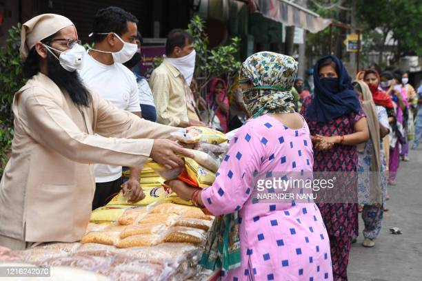 A Hindu priest along with volunteers distribute grocery items to people in need after the government eased a nationwide lockdown as a preventive...