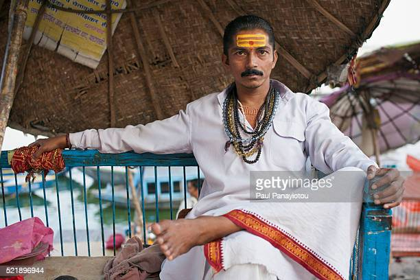 a hindu priest at dasaswamedh ghat offers blessings and prayers to pilgrims, varanasi, india - brahmin stock pictures, royalty-free photos & images