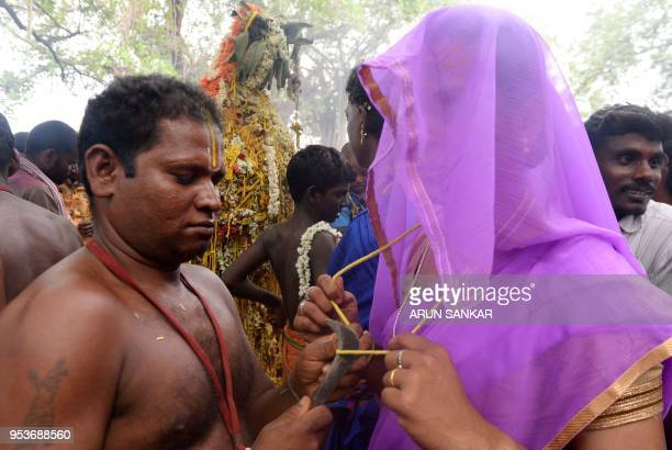 A Hindu priest cuts the 'thali' sacred thread and bangles of an Indian transgender devotee following a ritual signifying their marriage to the Hindu...