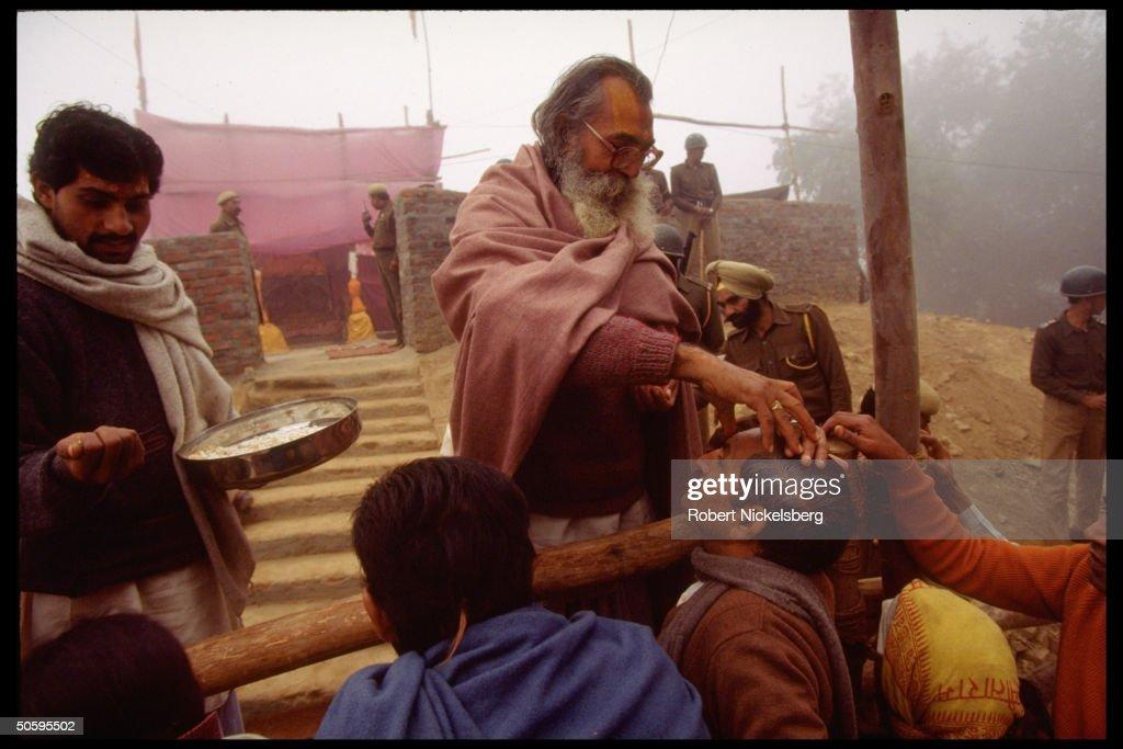 Hindu priest & devotees during darshan ( : News Photo