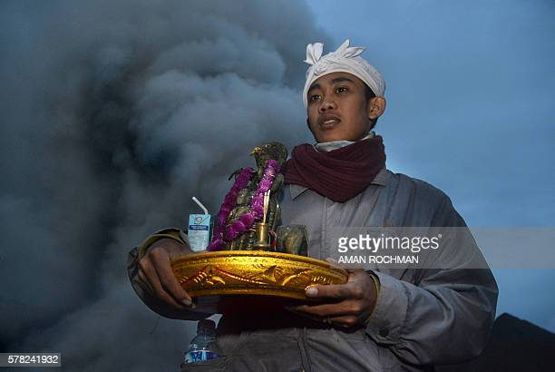 A Hindu priest from the Tengger tribe holds offerings during the Yadnya Kasada festival on the crater of Mount Bromo in Probolinggo on July 21 2016...