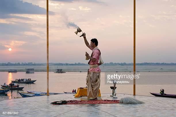 Hindu priest in prayer ritual at sunrise by the Ganges river in Varanasi, India