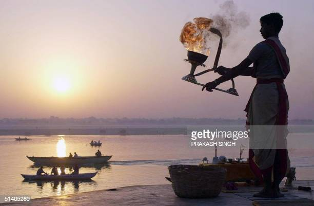Hindu priest offers prayers to the rising sun on the banks of the Ganges at Benares 06 December 2001 Many devout Hindus journey to Benares one of...
