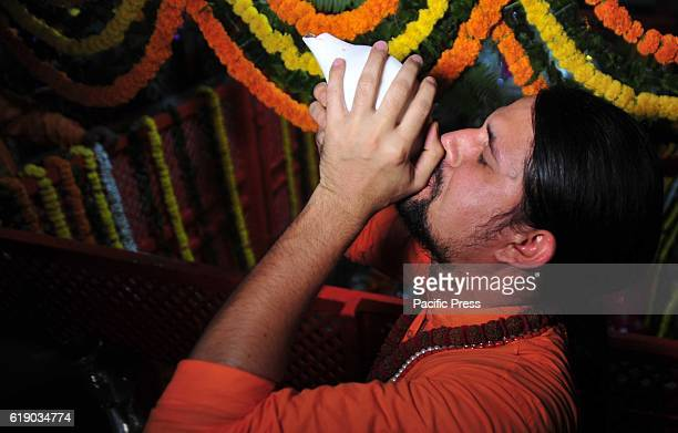 Hindu priest playing conch shell during offering prayer on the occasion of Hanuman Jayanati Festival in Allahabad Hanuman Jayanati is dedicated to...