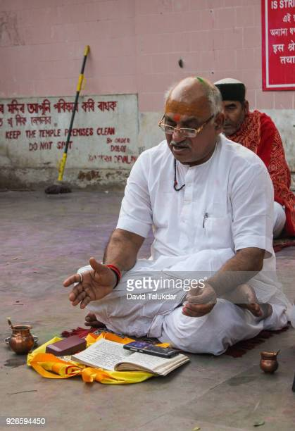 Hindu priest reading mythological book at Kamakhya Temple.
