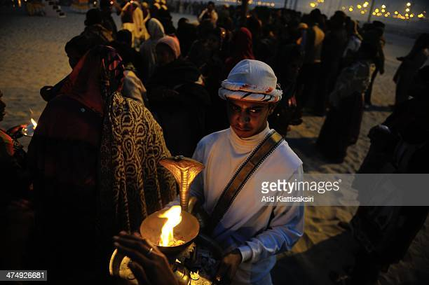 Hindu priest receives alms during the Ganga Aarati ceremony at the Sangam, the confluence of Yamuna, Ganges and mythical Saraswati rivers during Maha...