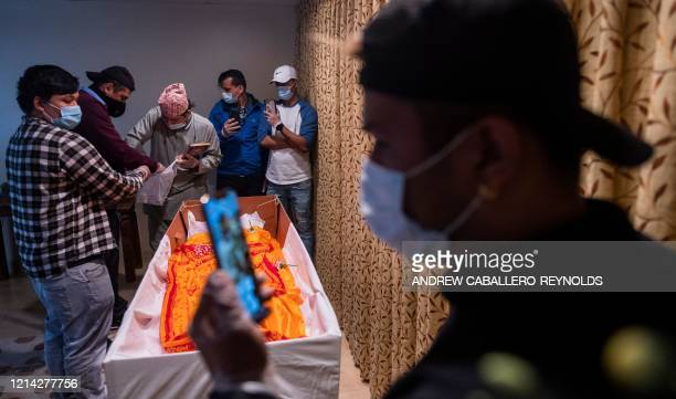 Hindu priest Shiva Devkota leads a funeral service as Pawan KC the cousin of the deceased Ashish KC performs funeral rites while others all wearing...