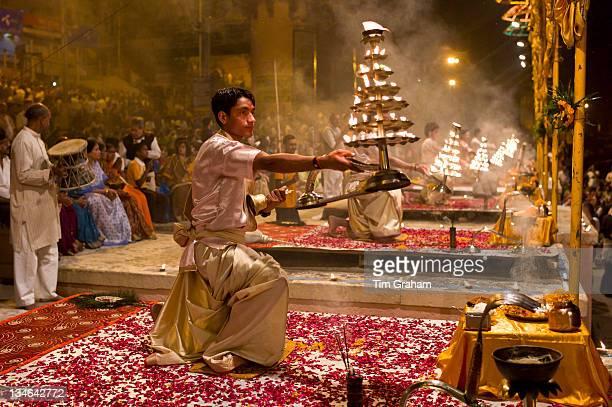 Hindu priests at sundown Aarti Ritual Ceremony of Light during Shivrati Festival in Holy City of Varanasi Benares India