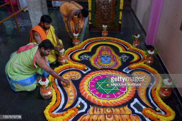Hindu priests draw a mandala a sacred geometric design drawn as part of a ritual held at a temple in Bangalore on March 18 to ward off the virus...