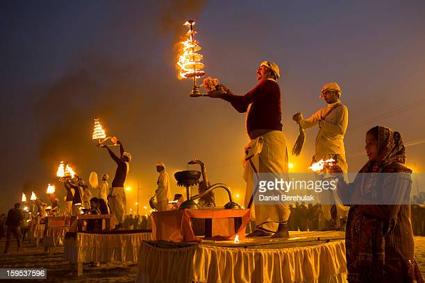 Hindu priests perform during an aarti ceremony on the banks of the Ganges river during the Maha Kumbh Mela on January 15 2013 in Allahabad India The...