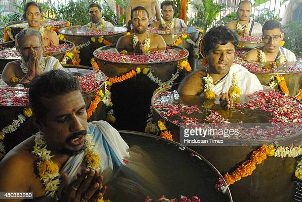 Hindu priests praying to rain god Varuna standing in chest deep water to shower his blessings in the form of early rain at Sankara Mattam Matunga...