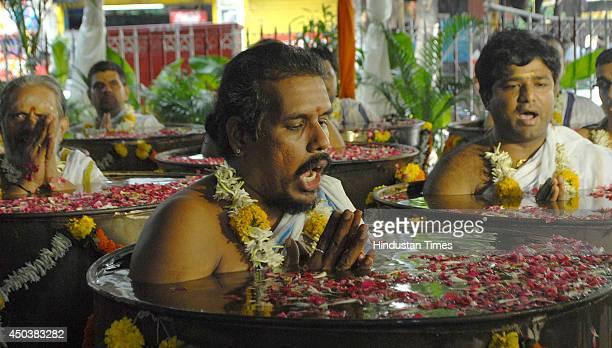 Hindu priests praying to rain god Varuna standing in chest deep water to shower his blessings in the form of early rain at Sankara Mattam Matunga...