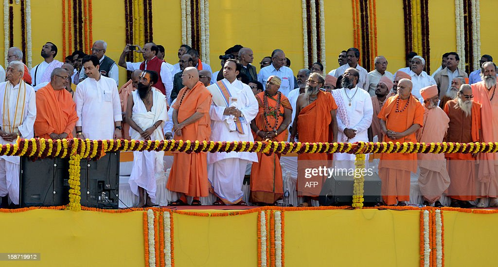 Hindu priests wait to greet newly sworn in Chief Minister of the western Indian state of Gujarat Narendra Modi during the swearing in ceremony of Modi at The Sardar Patel Navrangpura Stadium in Ahmedabad on December 26, 2012. Modi who won a landslide victory in recent state assembly polls, was administered the oath of office and secrecy by Gujarat Governor Kamla Beniwal at a ceremony which was attended by many senior BJP leaders. AFP PHOTO/Sam PANTHAKY