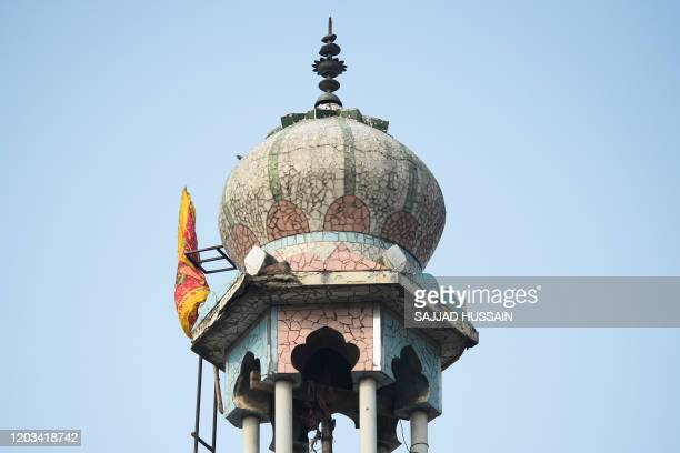 Hindu religious flag is seen on a minaret of a burnt-out mosque following clashes between people supporting and opposing a contentious amendment to...