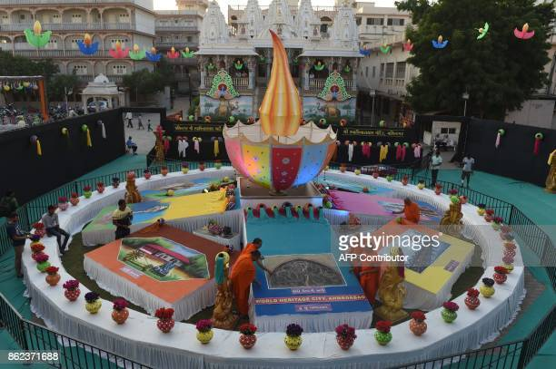 Hindu religious men from the Swaminarayan Gadi Sansthan Maninagar temple put the final touches on a huge piece of folk art a Rangoli ahead of Diwali...