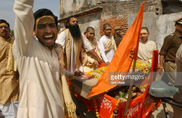 Hindu religious men move two stone pillars to where the stones will be ceremonially blessed March 15 2002 in the northern Indian city of Ayodhya The...
