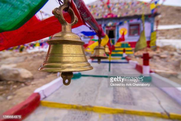 hindu religious prayer bell with buddhist prayer flags, ladakh, india - bell stock pictures, royalty-free photos & images