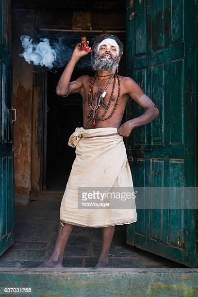 Hindu Sadhu holy man smoking charas outside temple Kathmandu Nepal