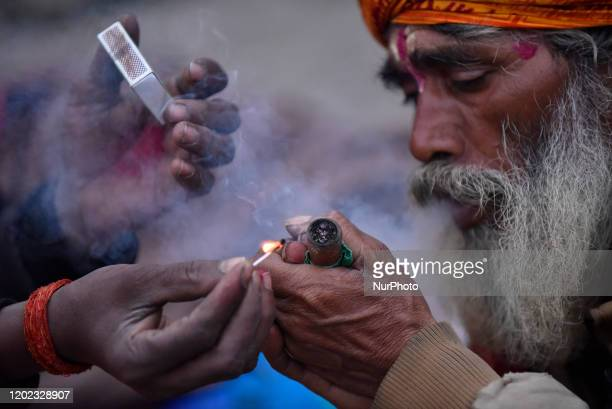 A Hindu Sadhu or Holy Man prepare to smoke marijuana in a Chillim during Maha Shivaratri at the premises of Pashupatinath Temple Kathmandu Nepal on...