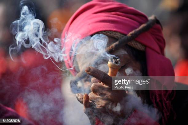 Hindu Sadhu or Holy Man smokes marijuana at the premises of Pashupatinath Temple during the celebration of Maha Shivaratri Festival at Kathmandu...
