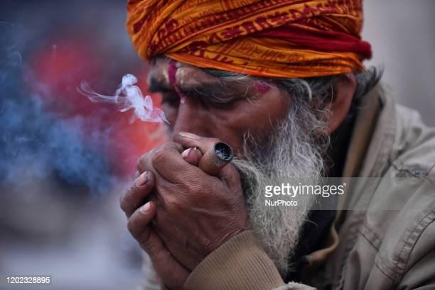 A Hindu Sadhu or Holy Man smokes marijuana in a Chillim during Maha Shivaratri at the premises of Pashupatinath Temple Kathmandu Nepal on Friday...