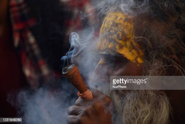 Hindu Sadhu or Holy Man smokes marijuana in a Chillim during Maha Shivaratri at the premises of Pashupatinath Temple, Kathmandu, Nepal on Thursday,...