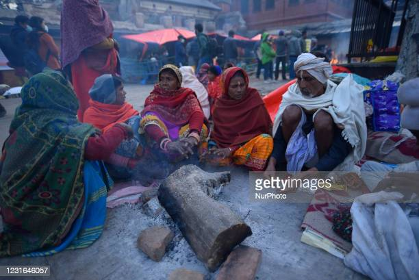 Hindu Sadhu or Holy Man warm themselves on a bonfire during Maha Shivaratri at the premises of Pashupatinath Temple, Kathmandu, Nepal on Thursday,...