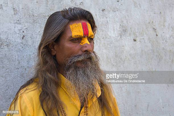 Hindu sadhu or holy man, with long hair and a beard, wearing traditional yellow and red paint, standing before a white wall, at the hindu temple...