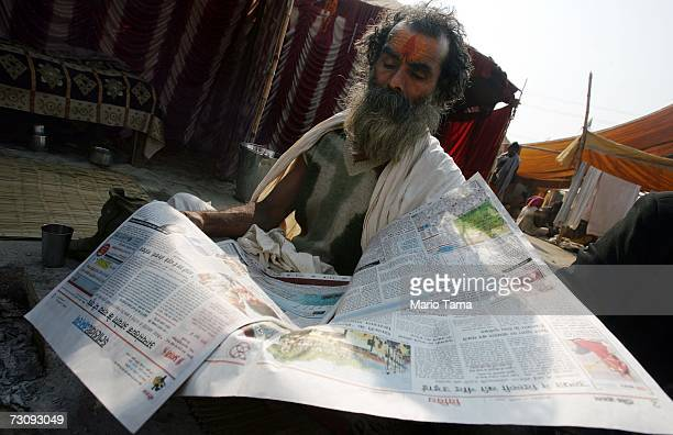 Hindu Sadhu reads a newspaper near the ritual bathing site at Sangam the confluence of the Ganges Yamuna and mythical Saraswati rivers during the...