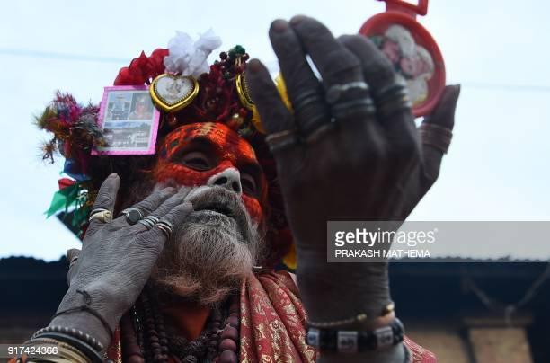 A Hindu sadhu smears coloured paste onto his face at the Pashupatinath temple in Kathmandu on Febuary 12 on the eve of the Hindu festival Maha...