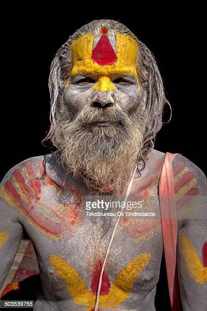 CONTENT] A hindu sadhu wearing traditional red yellow and white paint sitting in the sun at the holy temple complex of Pashupatinath along the...
