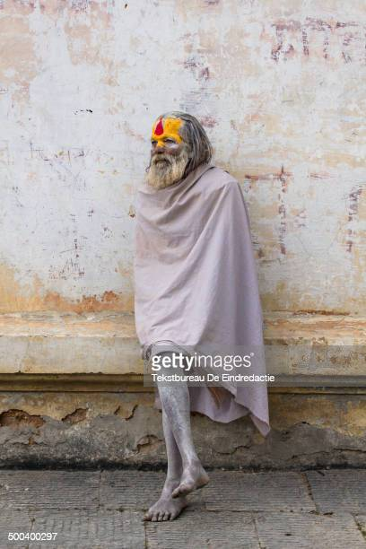 Hindu sadhu , wrapped in a white blanket, sitting on a ledge at the temple complex of Pashupatinath along the Bagmati River, one of the holiest...
