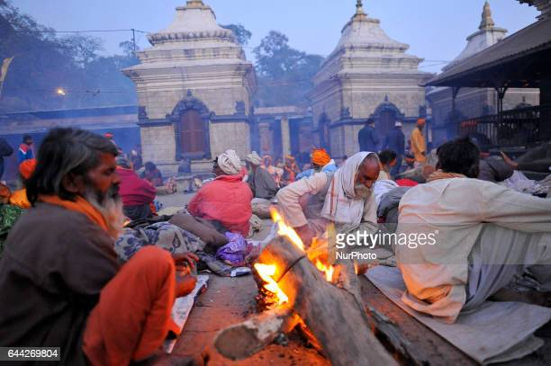 A Hindu Sadhus or Holy Man warm themselves on fire in a evening at the premises of Pashupatinath Temple Kathmandu Nepal on Thursday February 23 2017...