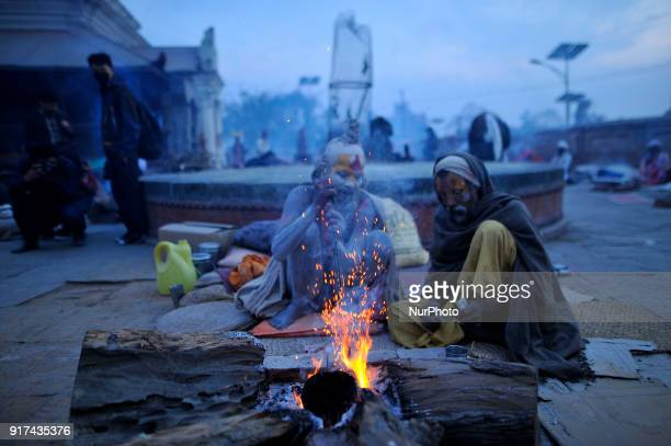 Hindu Sadhus or Holy Man warm themselves on wood fire in a evening at the premises of Pashupatinath Temple Kathmandu Nepal on Monday February 12 2018...