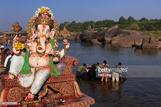 Hindu statue of Ganesha and western tourists with mahouts cleaning the elephant Lakshmi in the Tungabhadra river in the background, Hampi, Karnataka,...