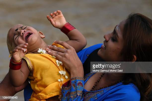 Hindu woman holds her baby near the river before the start of a prayer during the Thaipusam festival on January 18 2019 outside Kuala Lumpur Malaysia...
