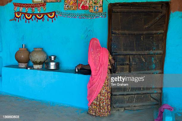 Hindu woman in traditional blue painted home in Hindu Brahman high caste village of Dhudaly in Rajasthan Northern India