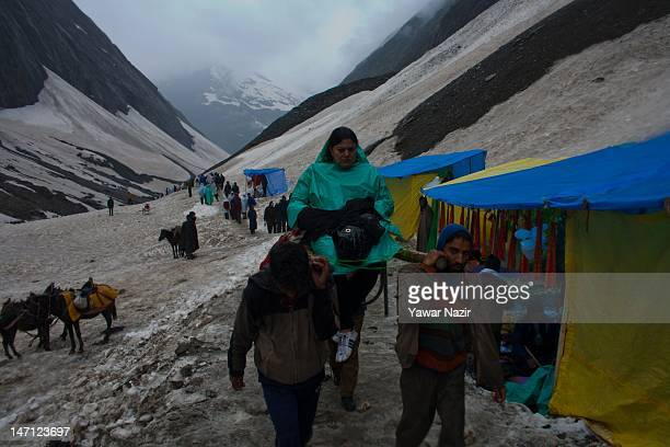 Hindu woman is carried back to the sacred cave by palanquin bearers near Amarnath cave one of the most revered of Hindu shrines in Baltal some 125 km...