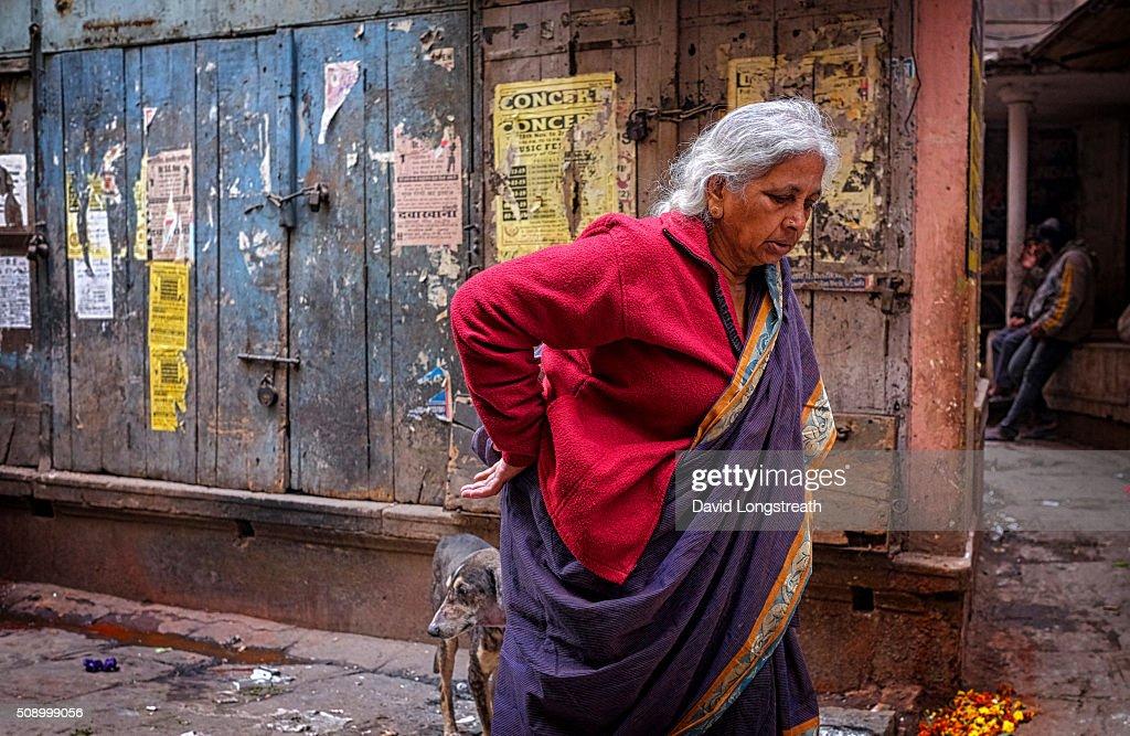 A Hindu woman makes her way along a narrow alley towards a... : News Photo