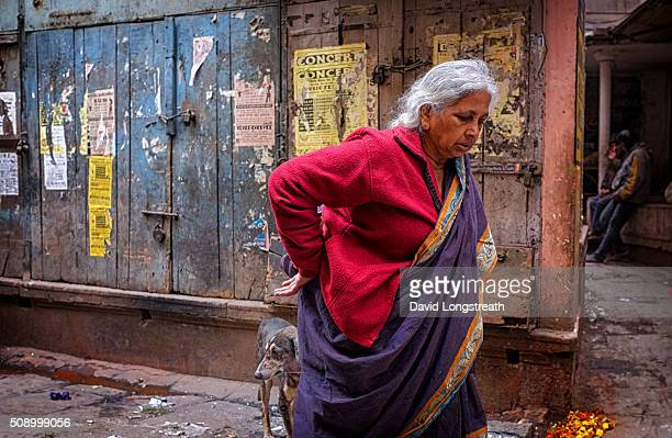 Hindu woman makes her way along a narrow alley towards a bathing Ghat on the Ganges
