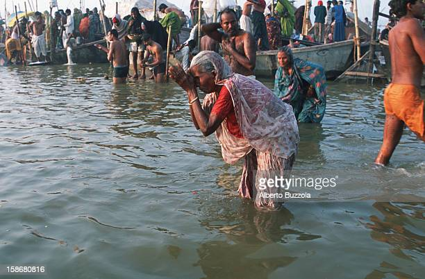Hindu woman performing Puja a traditional Hindu prayer at the Holy Sangam the confluence of the three most sacred rivers of the country the Ganges...