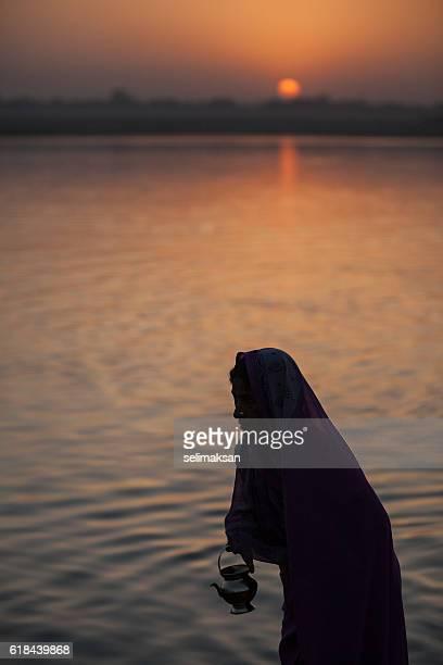Hindu Woman Praying At Sunrise In Ganges River, Varanasi