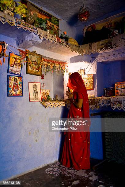 A hindu woman prays at the improvised altar with deities and statues inside the family's Salawas Rajasthan India | Location Salawas Rajasthan India