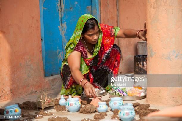 hindu woman  preparing flowers and cow dung for puja offerings in varanasi - fotofojanini foto e immagini stock